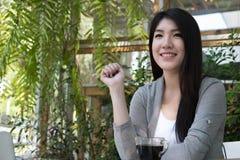 La donna asiatica si siede al caffè all'aperto giovane adulto femminile con naturale Immagini Stock