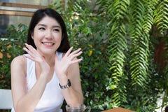 La donna asiatica si siede al caffè all'aperto giovane adulto femminile con naturale Fotografie Stock Libere da Diritti