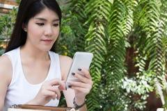La donna asiatica si siede al caffè all'aperto giovane cellulare adulto femminile p di uso Fotografia Stock