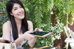 La donna asiatica si siede al caffè all'aperto giovane tenuta adulta femminile digitale Immagini Stock Libere da Diritti