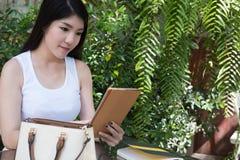 La donna asiatica si siede al caffè all'aperto giovane uso adulto femminile digitale Fotografia Stock Libera da Diritti