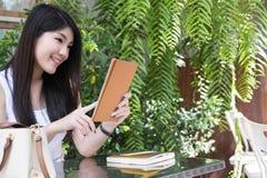 La donna asiatica si siede al caffè all'aperto giovane uso adulto femminile digitale Immagini Stock