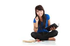 La donna asiatica si siede con un libro Fotografia Stock