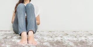 La donna asiatica si siede sul pavimento di tappeto grigio con il fondo strutturato del cemento bianco all'angolo della casa con  fotografie stock libere da diritti