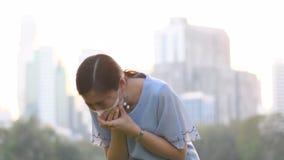 La donna asiatica sta indossando la maschera della protezione per proteggere il cattivo inquinamento atmosferico PM2 5 stock footage