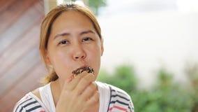 La donna asiatica sta mangiando l'alimento del dolce della ciambella video d archivio