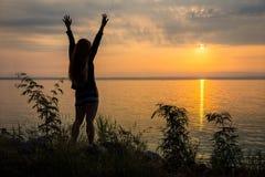 La donna asiatica sta rinfrescando alzando le armi sulla riva del fiume all'alba Fotografia Stock