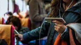La donna asiatica sta su nel treno Facendo uso dello smartphone in sottopassaggio fotografia stock libera da diritti