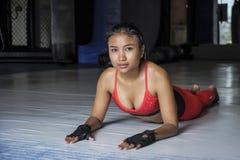La donna asiatica sudata bella giovane nello sport copre l'allungamento sulla posa sorridente del pavimento del dojo della palest Fotografie Stock