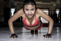 La donna asiatica sudata sexy in vestiti che di sport fare spinge aumenta sul pavimento del dojo della palestra che sorride nell' Fotografie Stock Libere da Diritti