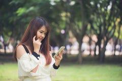 La donna asiatica sveglia sta leggendo il messaggio di testo piacevole sul telefono cellulare mentre si sedeva nel parco nel gior Immagini Stock