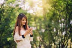 La donna asiatica sveglia sta leggendo il messaggio di testo piacevole sul telefono cellulare mentre si sedeva nel parco nel gior Fotografia Stock Libera da Diritti