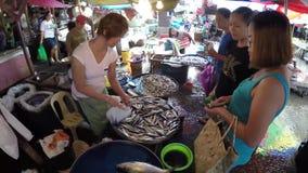 La donna asiatica vende il vario pesce al mercato bagnato della stalla video d archivio