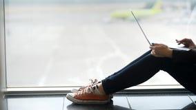 La donna astuta e rilassata sta sedendosi vicino alla finestra ed alle informazioni di battitura a macchina sul computer portatil stock footage