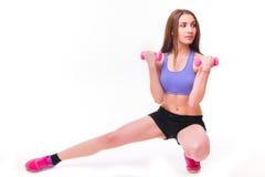La donna atletica allegra attiva con le teste di legno che pompano su muscles il bicipite fotografie stock