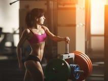 La donna atletica brutale che pompa su muscles con Fotografia Stock Libera da Diritti