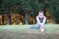 La donna atletica che fa l'allungamento si esercita all'aperto fotografia stock