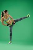 La donna atletica che prepara il suo massimo dà dei calci dentro allo studio sul backgro verde Immagini Stock