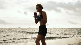 La donna atletica di karatè fa la scossa laterale delle sue gambe contro il sole dal mare al rallentatore Bello pugile femminile stock footage