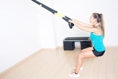 La donna atletica fa l'esercizio di TRX Fotografia Stock Libera da Diritti