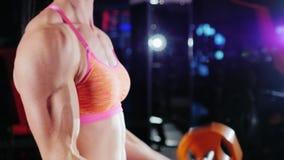 La donna atletica prepara i muscoli delle mani con un bilanciere culturismo femminile archivi video