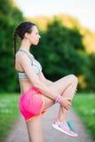 La donna attiva che fa la routine di riscaldamento nel parco prima dell'correre, allungando la gamba muscles con stare il singolo Immagini Stock Libere da Diritti