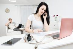 La donna attiva con i capelli neri lunghi sta chiamando in lavoratore anteriore e biondo nei precedenti immagini stock libere da diritti