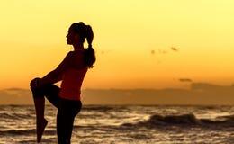 La donna attiva nello sport copre sull'allungamento della spiaggia Immagini Stock Libere da Diritti