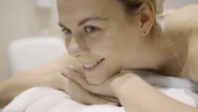 La donna attraente è sul massaggio posteriore in clinica all'interno archivi video