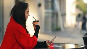 La donna attraente alla moda beve il caffè ed utilizza uno smartphone che si siede ad una tavola in un caffè sulla via video d archivio