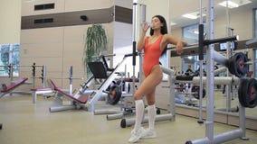 La donna attraente beve l'acqua da imbottiglia il simulatore alla società polisportiva stock footage