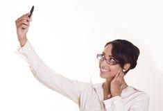 La donna attraente cattura una maschera del telefono delle cellule. Immagini Stock