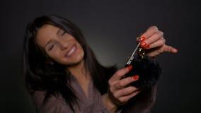 La donna attraente che tiene la nuova casa digita la sua mano e la mostra alla macchina fotografica archivi video