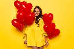 La donna attraente con cuore ha modellato gli aerostati che celebra il giorno del ` s del biglietto di S. Valentino fotografia stock libera da diritti