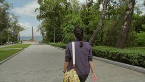 La donna attraente di Yound cammina verso il monumento vicino al mare Il colpo dalla parte posteriore video d archivio