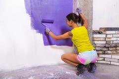La donna attraente dipinge il rullo bianco di porpora della parete immagini stock