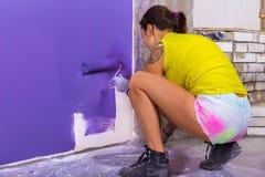 La donna attraente dipinge il rullo bianco di porpora della parete fotografia stock