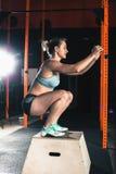 La donna attraente fa gli esercizi di sedere-UPS Esercizio di allenamento alla classe della palestra Fotografia Stock