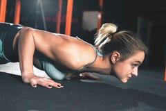 La donna attraente fa gli esercizi di sedere-UPS Esercizio di allenamento alla classe della palestra Immagini Stock Libere da Diritti