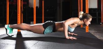 La donna attraente fa gli esercizi di sedere-UPS Esercizio di allenamento alla classe della palestra Fotografia Stock Libera da Diritti