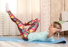 La donna attraente fa l'esercizio di forma fisica a casa su una stuoia blu in salone dopo avere svegliato Immagini Stock Libere da Diritti