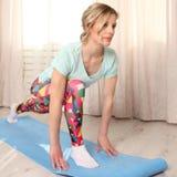 La donna attraente fa l'esercizio di forma fisica a casa su una stuoia blu in salone, mattina Fotografia Stock Libera da Diritti