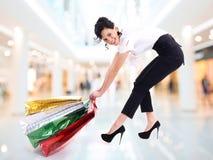 La donna attraente felice trascina i sacchetti della spesa. Fotografie Stock Libere da Diritti
