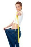 La donna attraente gli mostra i vecchi jeans enormi, dieta Immagine Stock