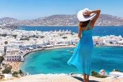 La donna attraente gode della vista sopra la città di Mykonos immagini stock