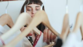 La donna attraente passa attraverso il suo guardaroba archivi video