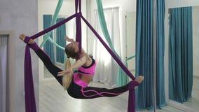 La donna attraente pratica l'yoga antigravità in amaca in studio video d archivio