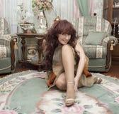 La donna attraente si siede su un pavimento. Immagini Stock