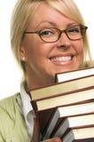 La donna attraente sorridente trasporta la pila di libri Fotografia Stock