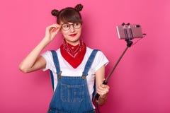 La donna attraente sta da solo sopra fondo rosa, facente il selfie mentre prova sui nuovi vetri alla moda, bastone del selfie di  immagini stock